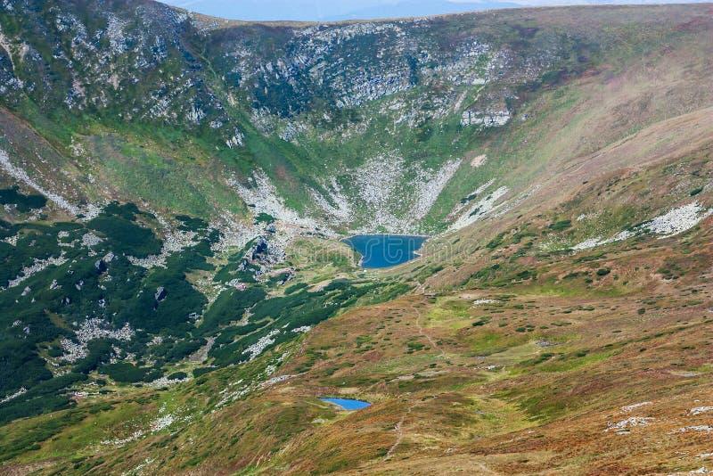 Panoramautsikt av en bergsjö i en dal för stenigt berg Fridfull sjö Berbeneskul, Carpathians, Ukraina arkivfoto