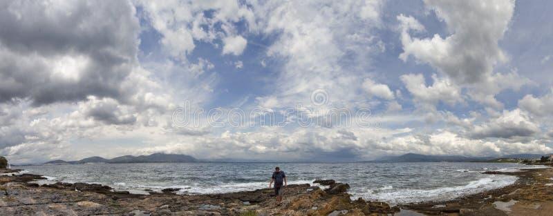 Panoramautsikt av en man på en stenig strand med att bedöva stormstackmolnmoln och vågor i det Aegean på en sommardag i den Evia  royaltyfri bild