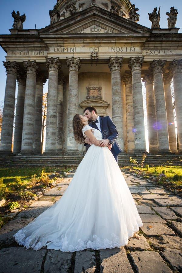 Panoramautsikt av ett saganygift personpar som kramar och kysser royaltyfri bild