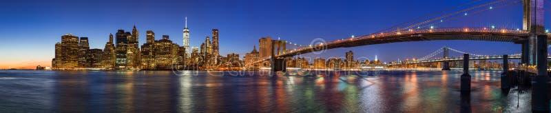 Panoramautsikt av finansiella områdesskyskrapor för Lower Manhattan på skymning med den Brooklyn bron och Eastet River New York royaltyfria bilder