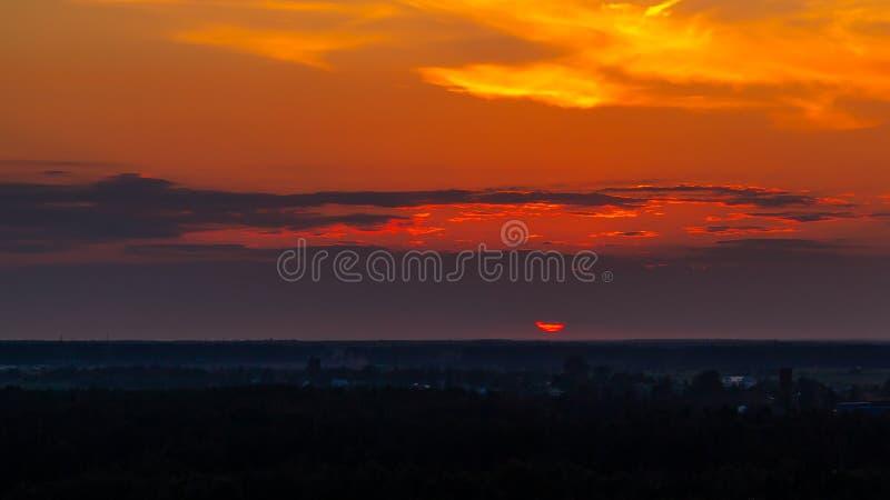 Panoramautsikt av horisonten och den färgrika solnedgången på utkanten av staden royaltyfri fotografi
