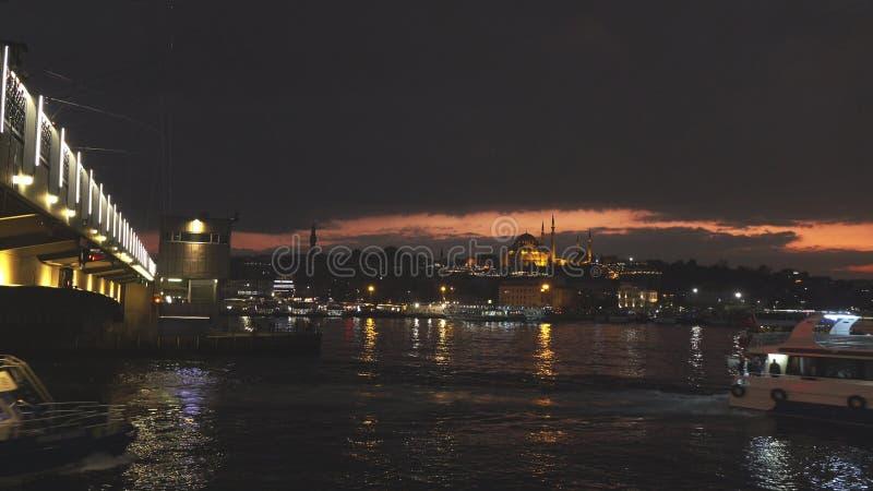Panoramautsikt av Istanbul cityscape med den Suleymaniye moskén med turist- skepp som svävar på Bosphorus på natten 4k UHD royaltyfri fotografi