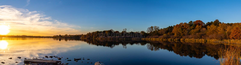 Panoramautsikt av solnedgången med nedgångfärger med reflexioner i sjön arkivfoton