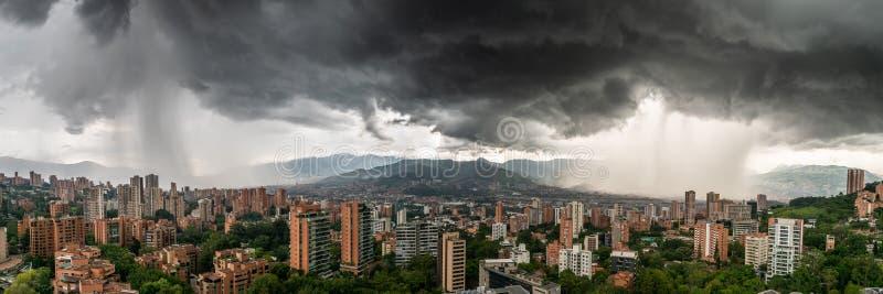 Panoramautsikt av två duschstormar som tvättar MedellÃn, i Colombia royaltyfri fotografi