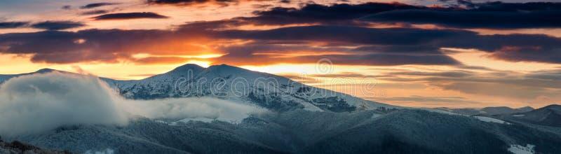 Panoramautsikt av vinterberg på soluppgång Landskap med dimmiga kullar och träd som täckas med rimfrost fotografering för bildbyråer