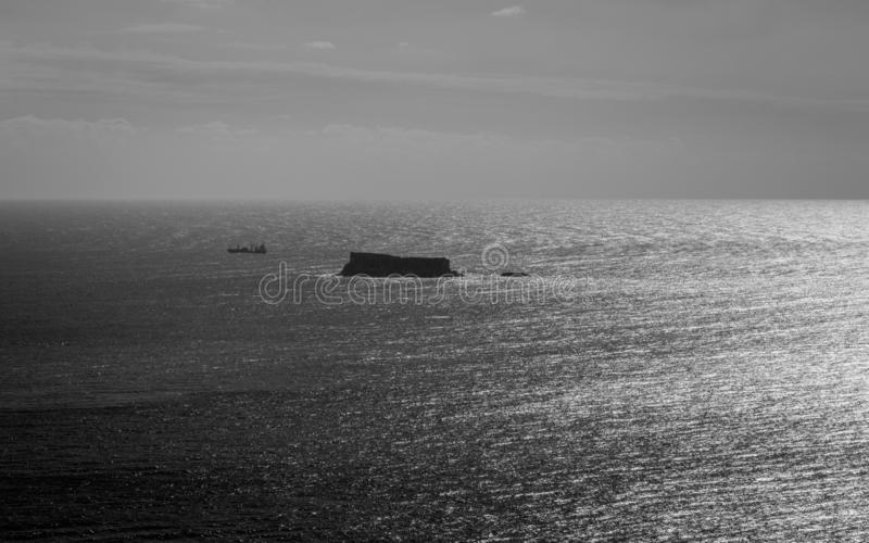 Panoramautsikt för hög kontrast på den maltesiska ön Filfla med ett trans.skepp i nära Klart hav på horisonten royaltyfri foto
