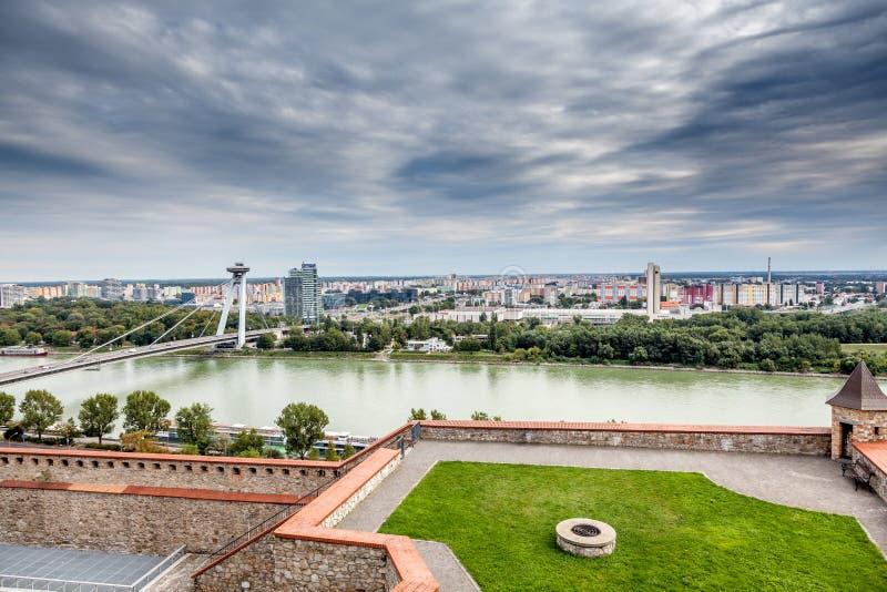 Panoramautsikt med dramatisk himmel över Bratislava horisont och flodDonau royaltyfria bilder