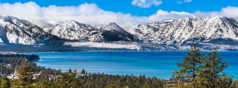 Panoramautsikt in mot Lake Tahoe på en solig klar dag; snön täckte toppiga bergskedjan berg i bakgrunden; vintergröna skogar in royaltyfria bilder