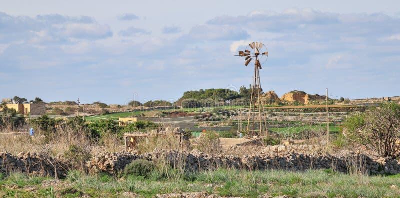 Panoramautsikt på ett härligt löst västra landskap med stenväggar, stugan och en bruten väderkvarn i Dingli, Malta på ett soligt, royaltyfria foton