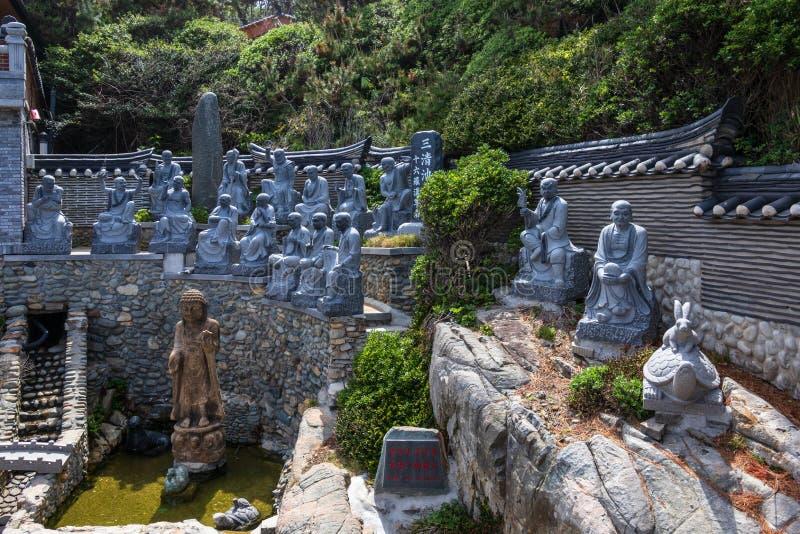 Panoramautsikt på många religiös buddistisk staty av be munkar i den koreanska Haedong Yonggungsa templet Busan Sydkorea, royaltyfri fotografi