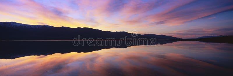 Panoramautsikt på solnedgången av översvämmade salta lägenheter och Panamint områdeberg i den Death Valley nationalparken, Kalifo fotografering för bildbyråer