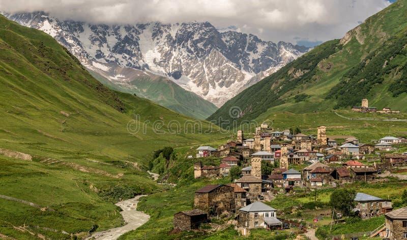 Panoramautsikten av byn Usghuli med den gamla stenen står högt under det högsta georgian berget Shkhara arkivfoto