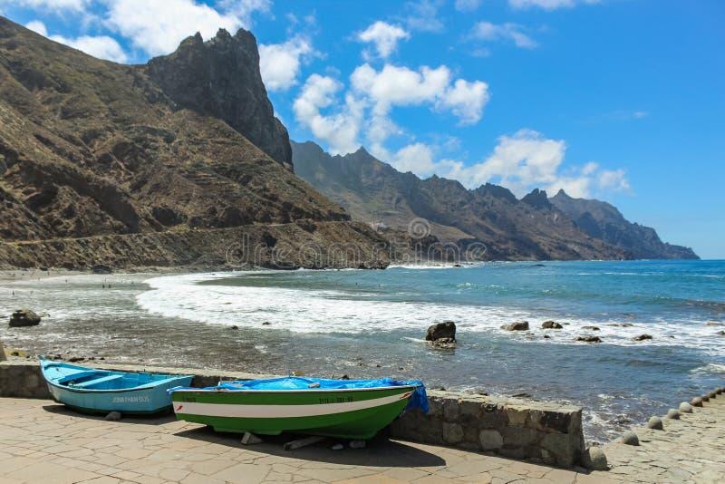 Panoramautsikten av den Aimasiga stranden med vulkanisk svart sand och ensamt vaggar att klibba ut ur havsskumet Lokala fiskebåta royaltyfria foton