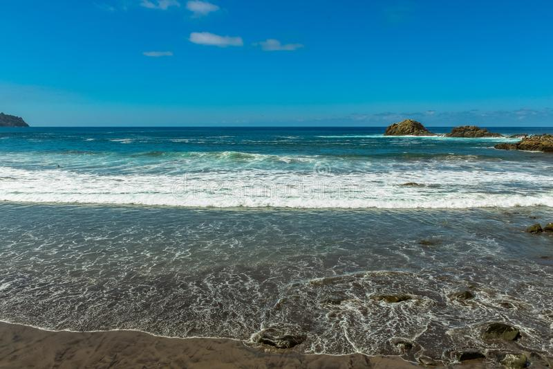 Panoramautsikten av den Aimasiga stranden med vulkanisk svart sand och ensamt vaggar att klibba ut ur havsskumet på norrkusten av arkivfoto