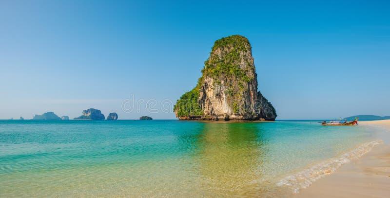 Panoramautsikten av den idylliska Railay stranden i Thailand med vaggar öar och en traditionell barkass royaltyfri bild