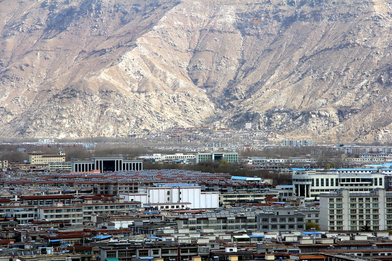 Panoramautsikten av den Lhasa staden som är främsta av Potala slott- och slottfyrkant, med moderna byggnad och berg, långt borta  arkivbild