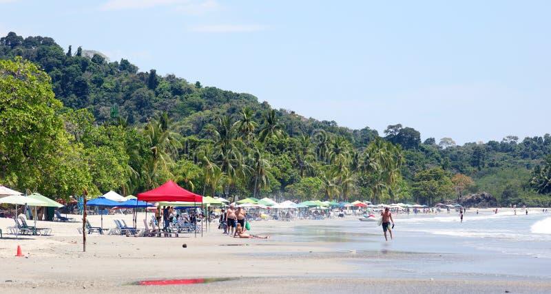 Panoramautsikten av den Manuel Antonio nationalparkstranden i Costa Rica, mest härlig stränder i världen, surfare sätter på land  arkivfoto