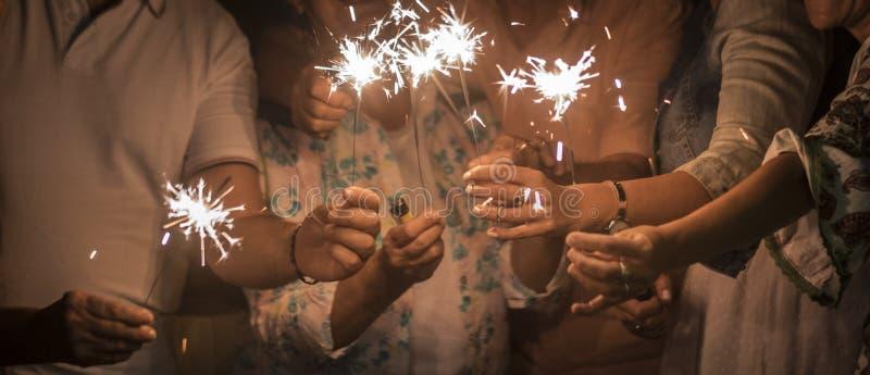 Panoramautsikten av gruppen av vänner blandade åldrar för att fira tillsammans i natten med mousserar mappljus helgdagsafton elle royaltyfri fotografi