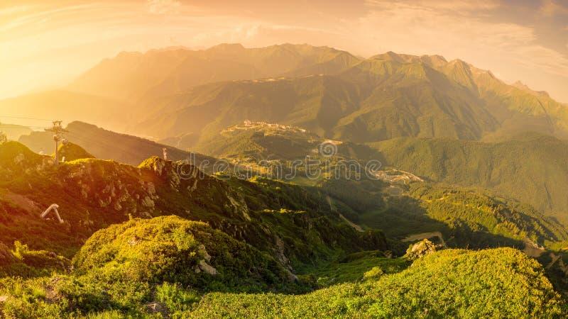 Panoramautsikten av solnedgången i sommar uppifrån av det Aibga området till skidar semesterorten Rosa Khutor Kabelbilen exponera royaltyfria foton