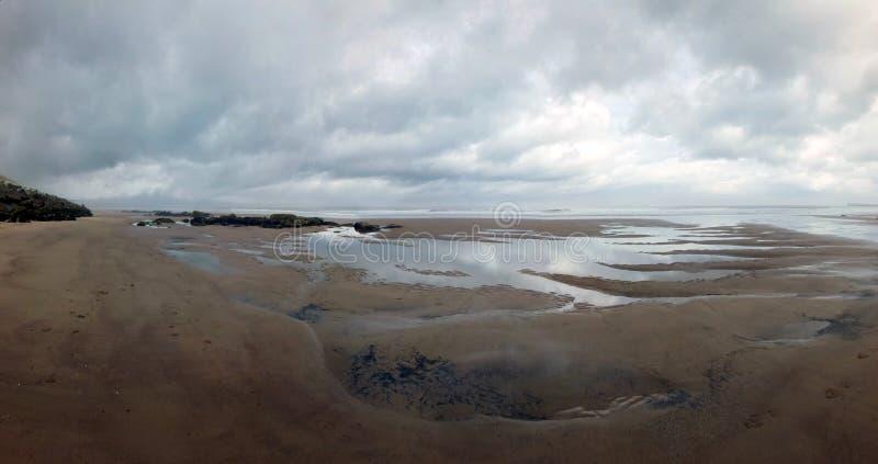 Panoramautsikten av stranden på sandsend nära whitby på lågvatten med en dramatisk stormig molnig himmel reflekterade i tips av v arkivfoton