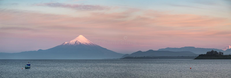 Panoramautsikten av suneten över sjön Llanquihue och snö täckte den Osorno vulkan, Puerto Varas, Patagonia, Chile royaltyfria bilder