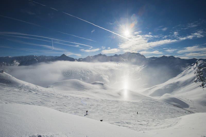 Panoramautsikten ner snö täckte dalen i alpin bergskedja med sundog arkivfoton