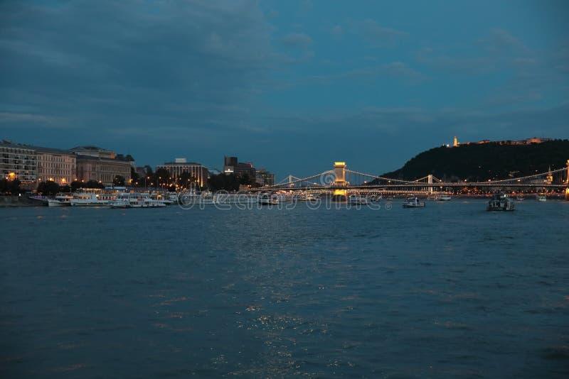 Panoramautsikter av nattbroar till och med Donau med belysning arkivbild