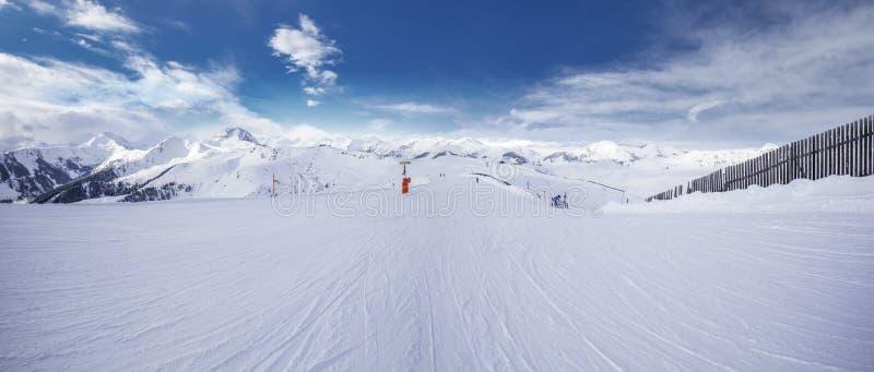 Panoramaview, который нужно кататься на лыжах наклоны и лыжники катаясь на лыжах в лыжном курорте горы Kitzbuehel с предпосылкой  стоковая фотография rf