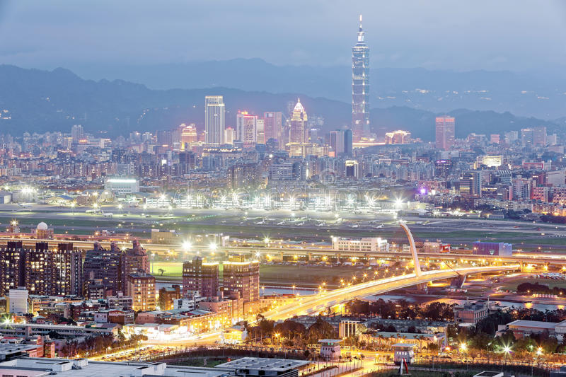Panoramic aerial view of busy Taipei City, Keelung River, Dazhi Bridge, Songshan Airport & 101 Tower in XinYi District at dusk stock image
