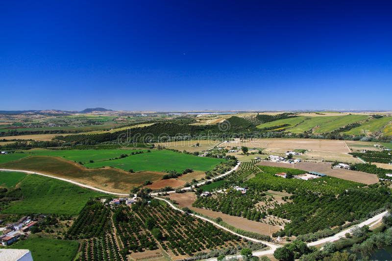 Panoramic aerial view from plateau of Ronda on endless rural plain with olive groves and crop fields under blue sky, Andalusia,. Ronda: ic aerial view from royalty free stock photos