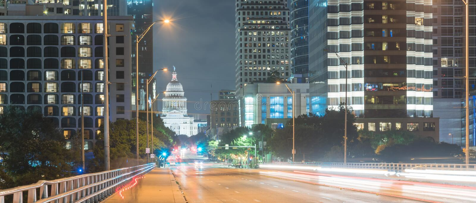 Panoramic Austin modern skylines and state capitol building at n. Panorama view downtown Austin at night with traffic light trail lead to Texas State capitol royalty free stock photography