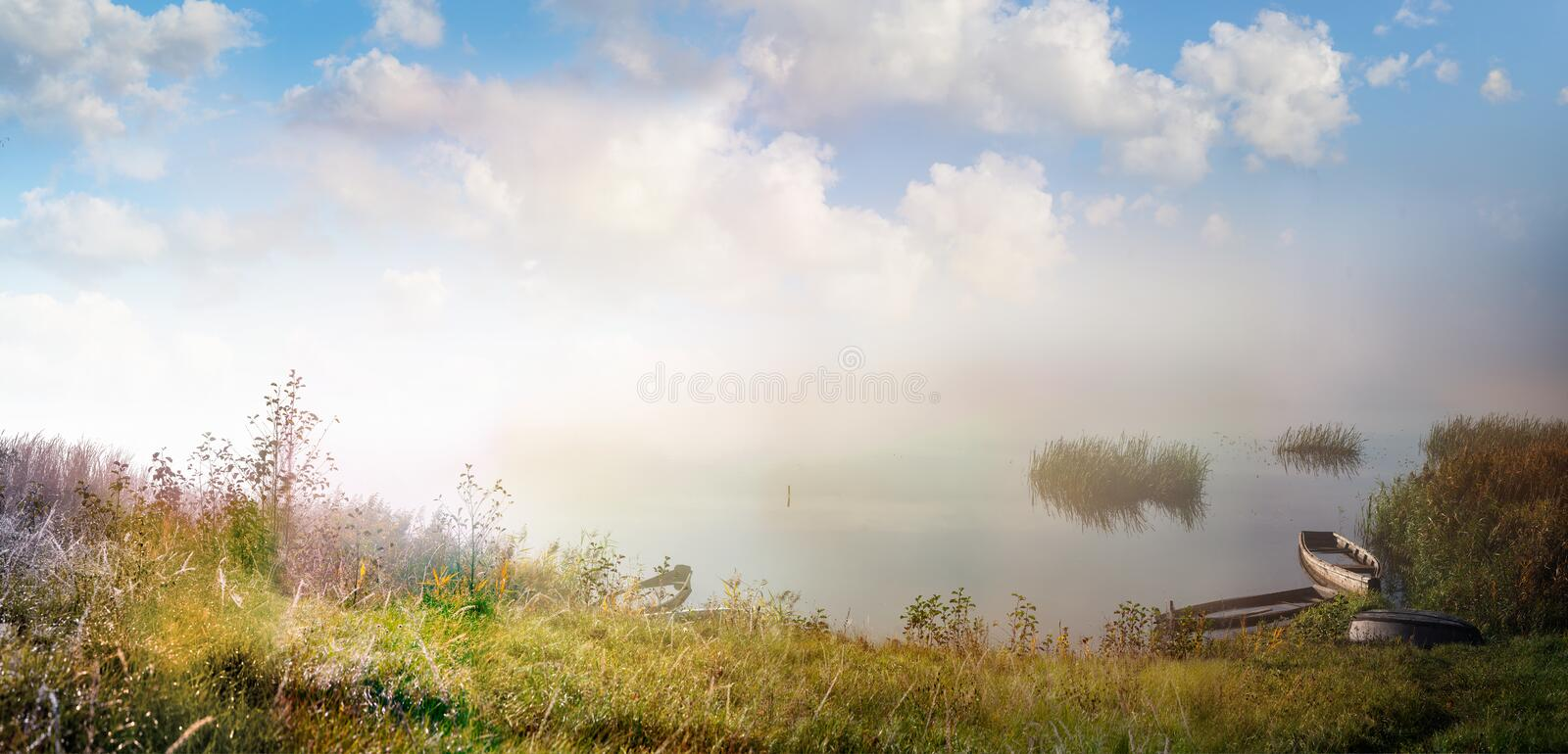Panoramic autumn landscape with boats on a water body shore stock photography