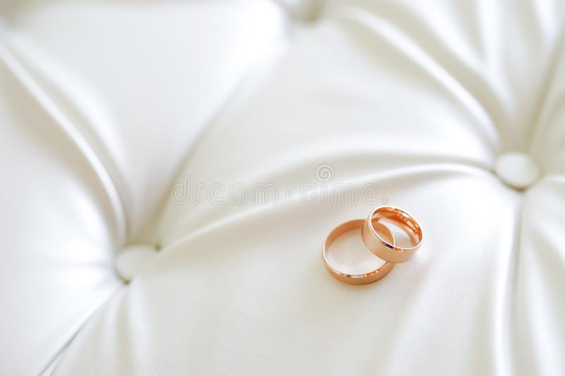Panoramic banner of two gold wedding rings symbolic of love and romance on a textured leather background with copy space for your stock images