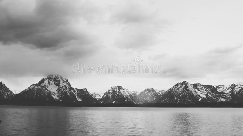 Panoramic beautiful grayscale photography of sea surrounded by mountains and grey clouds. A panoramic beautiful grayscale photography of sea surrounded by stock images