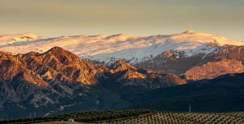 Panoramic beautiful view of Sierra Nevada snowcapped mountain range during golden hour, Spain. Panoramic beautiful view of Sierra Nevada snowcapped mountain royalty free stock photography
