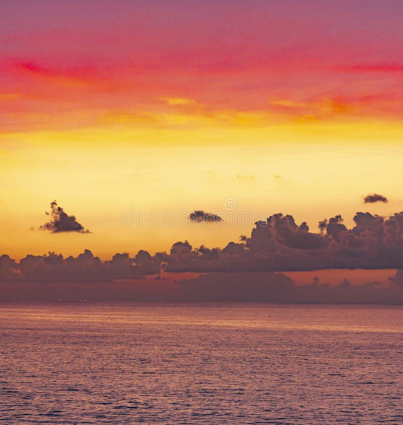 Panoramic beautiful view on sunset over the ocean. ?olorful cloudy gradient sky at evenig. multilayer clouds in the balinese sky royalty free stock images