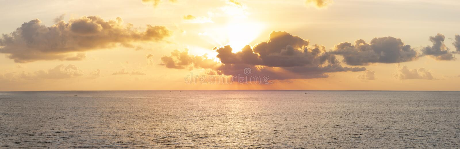 Panoramic beautiful view on sunset over the ocean. ?olorful cloudy sky and setting sun stock photos