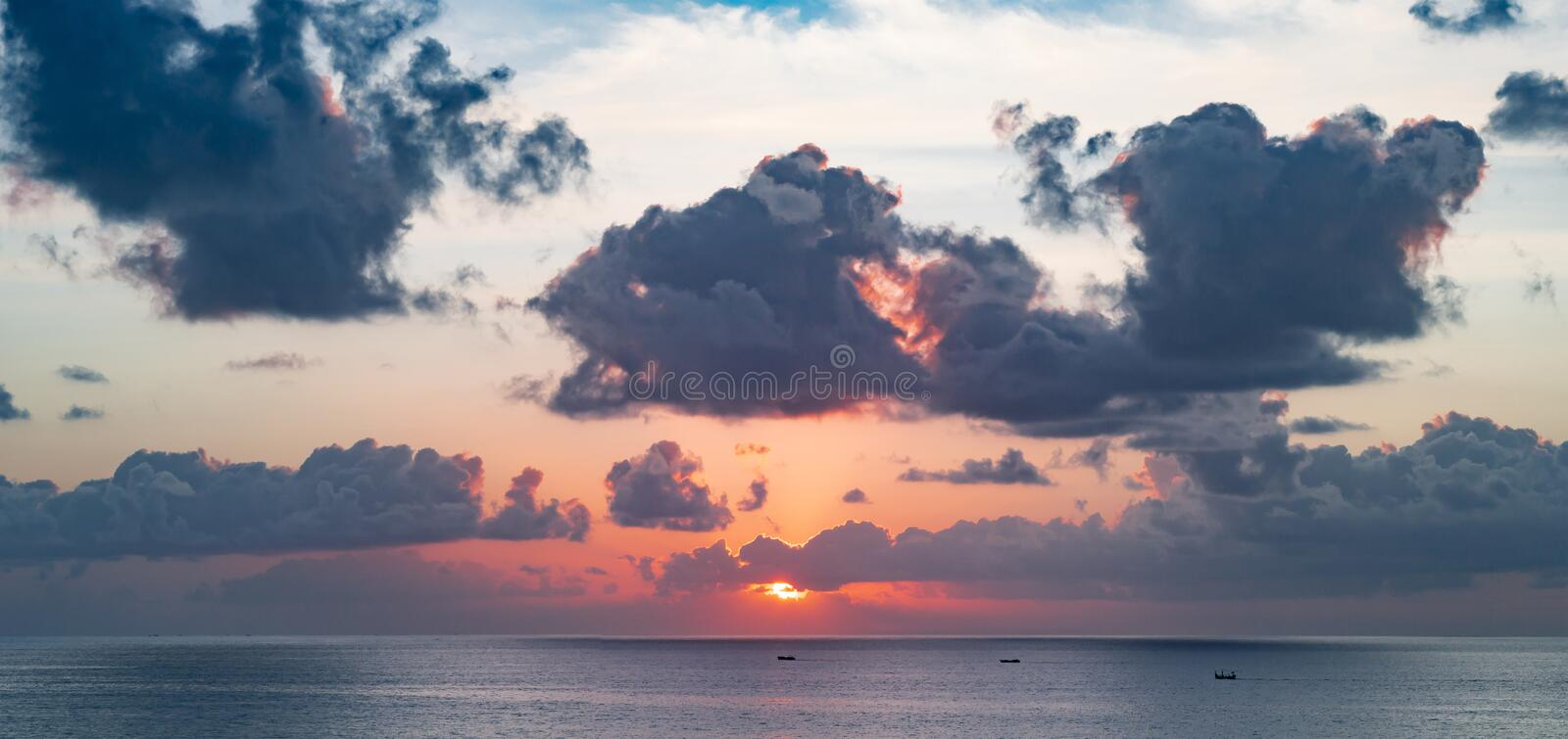 Panoramic beautiful view on sunset over the ocean. ?olorful cloudy sky and setting sun. Multilayer clouds in the balinese sky royalty free stock photos