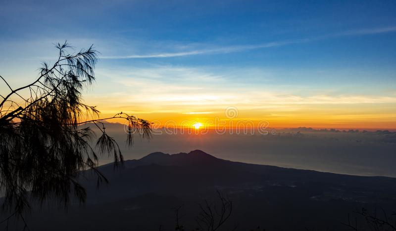 Panoramic beautiful view from top of the volcano Agung at dawn. View of the rising sun and Rinjani mount on the horizon from a royalty free stock photography