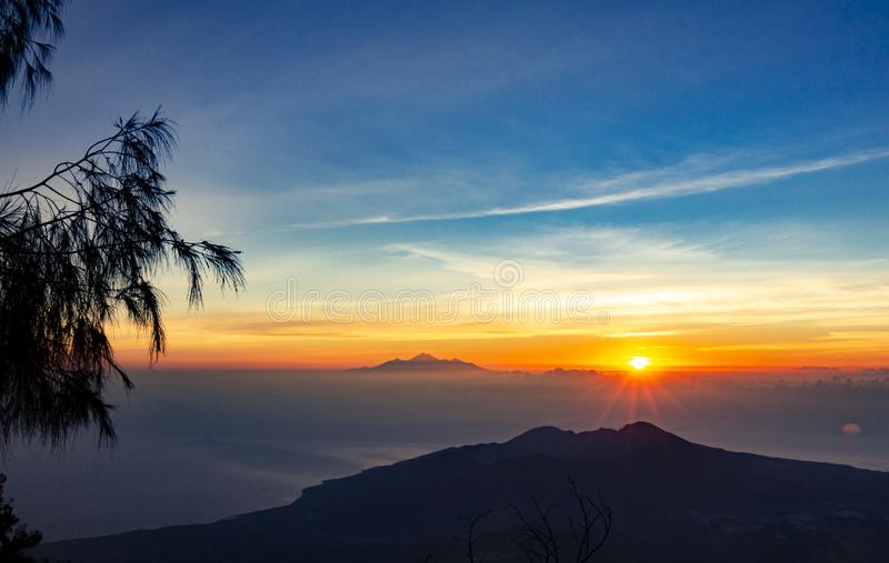 Panoramic beautiful view from top of the volcano Agung at dawn. View of the rising sun and Rinjani mount on the horizon from a. Height royalty free stock photos