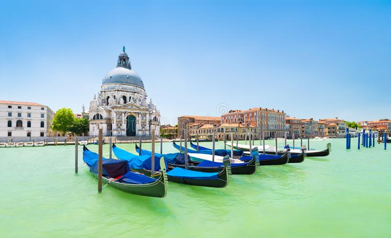 Panoramic view of traditional venetian gondolas moored in water of Grand Canal in front of Basilica di Santa Maria della Salute stock photos