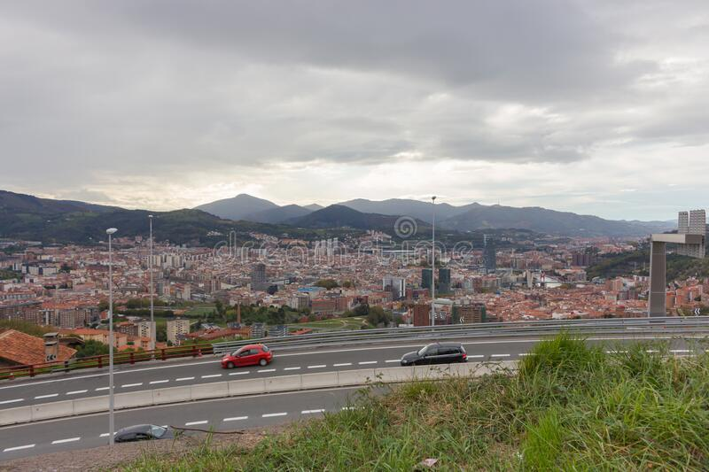 Panoramic Bilbao landmark with highway and cars. Aerial view of Bilbao, Spain. Road to capital of Basque country, Spain. Bilbao with mountains on background stock images