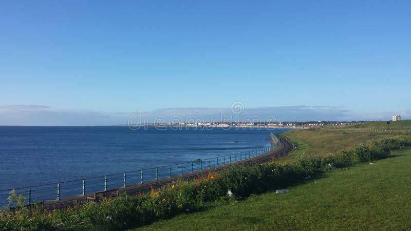 Panoramic Blue Sky British Coastline Beach. North East England on a beautiful sunny clear skies day with calm seas stock photos