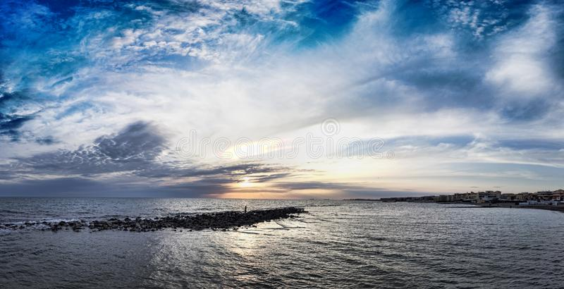 Panoramic blue sunset on Roman coast at Ostia Lido, with the intense sky the calm sea and a relaxing atmosphere. Panoramic pastel-colored sunset on the coast of stock image