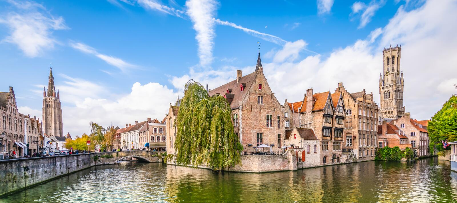 Panoramic city view Belfry tower and famous canal in Bruges, Belgium. Popular view point with belgian brick buildings along the canal. Church and belfry tower royalty free stock photography