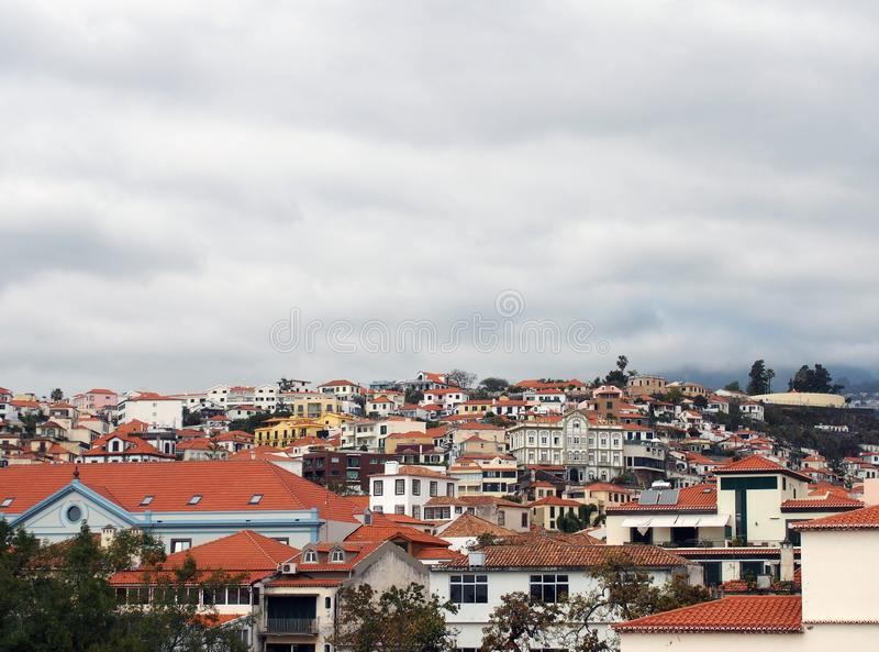 Panoramic cityscape view of funchal showing buildings of the town center and houses running up the mountains to trees and sky royalty free stock photo