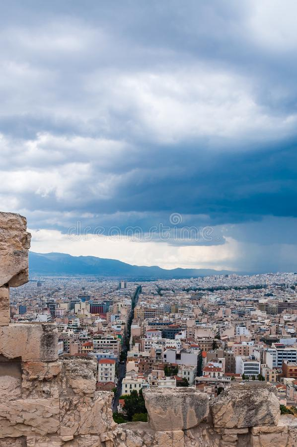 Panoramic cityscape view on Greece capital Athens city from Acropolis hill. View through ancient ruined stones on straight street. Athens, Greece - June 12, 2013 stock photography