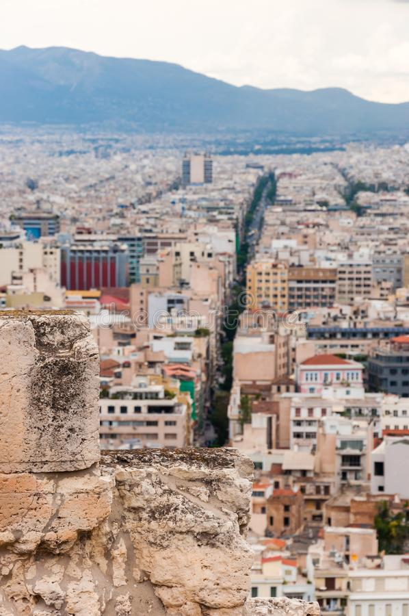 Panoramic cityscape view on Greece capital Athens city from Acropolis hill. View through ancient ruined stones on straight street. Athens, Greece - June 12, 2013 royalty free stock photos