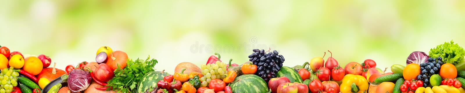 Panoramic collection fresh fruits and vegetables on green background. royalty free stock images
