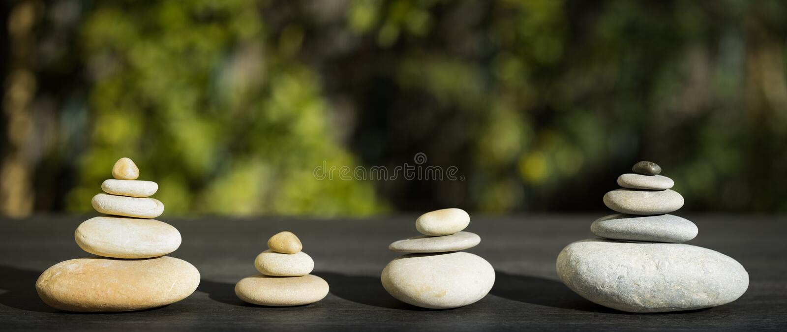 Panoramic composition with four stacking of stones. 4 stacks of pebbles of different sizes symbolizing a family stock photos